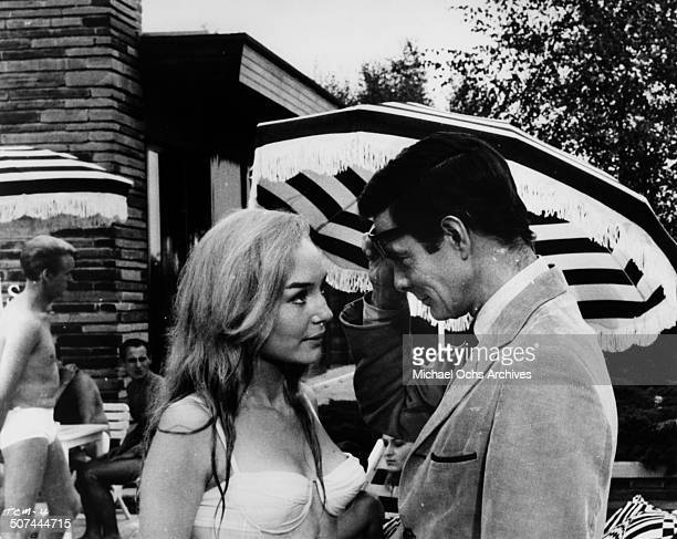 Louis Jourdan greets a new friend in a scene from the movie To Commit a Murder circa 1967