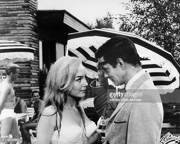 Louis Jourdan is greeted by a new friend in a scene from the film 'To Commit a Murder' 1967