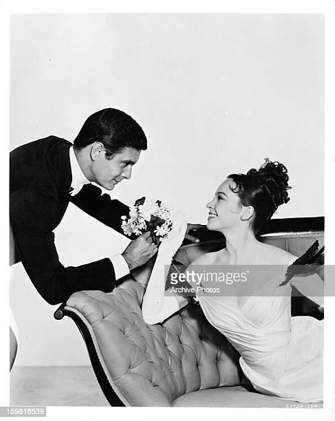 Louis Jourdan offering flowers to Leslie Caron in publicity portrait for the film 'Gigi' 1958