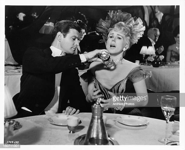 Louis Jourdan pouring drink on Eva Gabor in a scene from the film 'Gigi' 1958