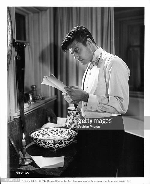 Louis Jourdan reads letter as he prepares to wash in a scene from the film 'Letter From An Unknown Woman' 1948