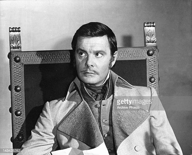 Louis Jourdan sitting and looking up to his right in a scene from the film 'The Young Rebel' 1967