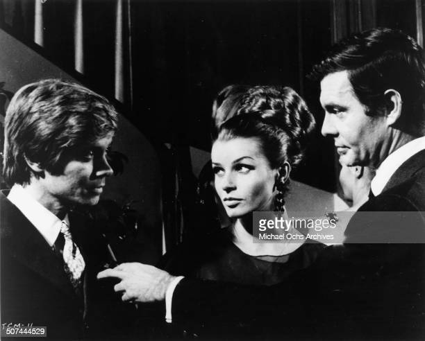 Louis Jourdan warns Fabrizio Capucci as Senta Berger stands in the middle in a scene from the movie To Commit a Murder circa 1967
