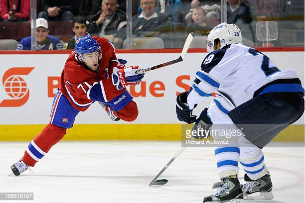Louis Leblanc of the Montreal Canadiens shoots the puck in front of Johnny Oduya of the Winnipeg Jets during the NHL game at the Bell Centre on...