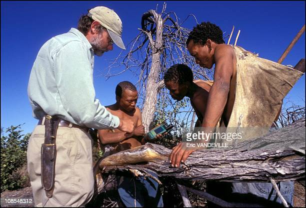 Louis Liebenberg explains three Bushman how to use the Cybertracker in Botswana in September 2001