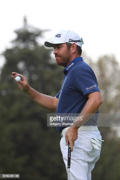 Louis Oosthuizen of South Africa acknowledges the fans after making a putt on the 18th plays a shot from the green of hole during the first round of...