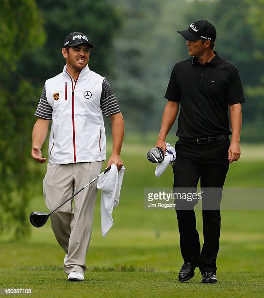 Louis Oosthuizen of South Africa and Matt Jones of Australia walk to the sixth hole during the first round of the Travelers Championship golf...