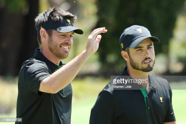 Louis Oosthuizen of South Africa and the International team congratulates Abraham Ancer of Mexico and the International team after his putt on the...