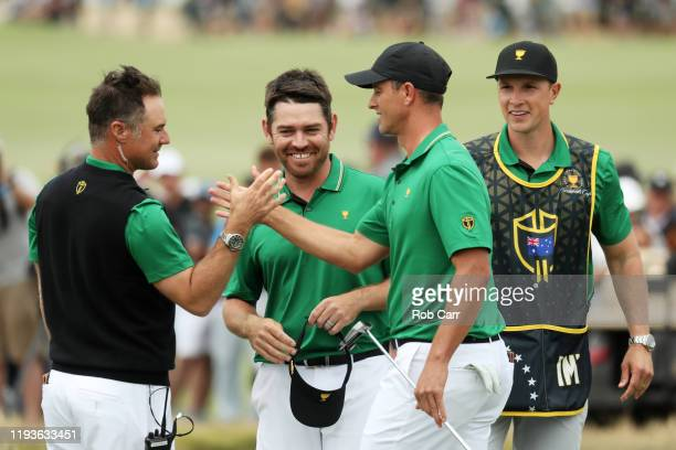 Louis Oosthuizen of South Africa and the International team and Adam Scott of Australia and the International team celebrate with Assistant Captain...