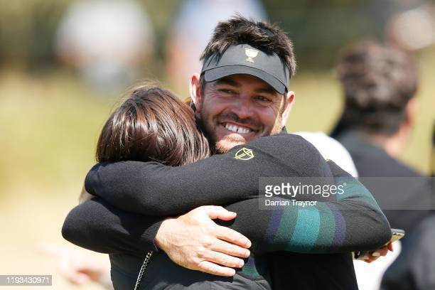 Louis Oosthuizen of South Africa and the International team hugs his wife NelMare Oosthuizen after he and Abraham Ancer of Mexico and the...
