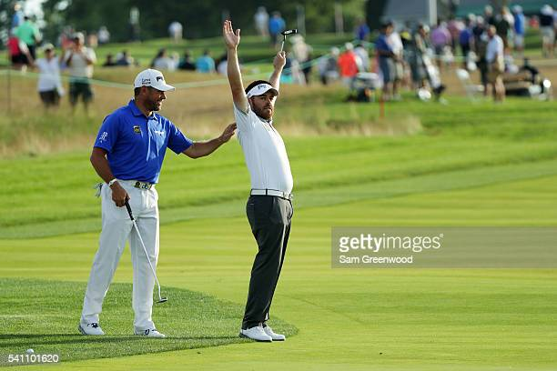 Louis Oosthuizen of South Africa celebrates a birdie alongside Lee Westwood of England on the tenth hole during the third round of the US Open at...