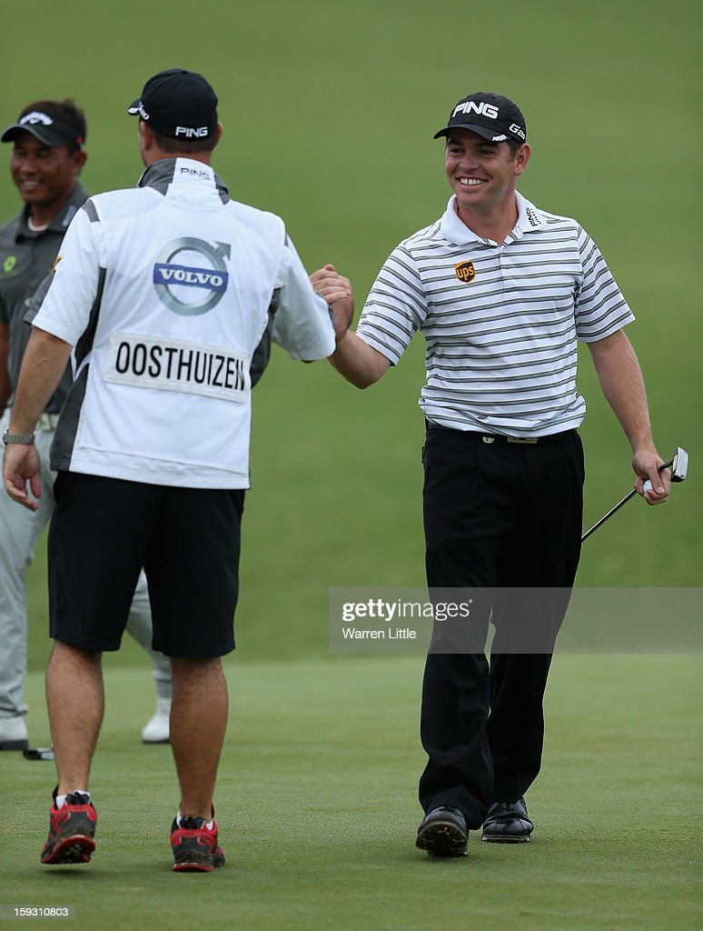 Louis Oosthuizen of South Africa celebrates his caddie Wynand Stander after holing a birdie putt on the 18th green to help his team win the pro-am competition during the second round of the Volvo Golf Champions at Durban Country Club on January 11, 2013 in Durban, South Africa.