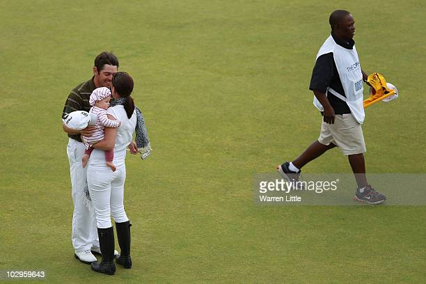 Louis Oosthuizen of South Africa celebrates his sevenstroke victory with his wife NelMare and daughter Jana and caddie Zack Rasego on the 18th green...