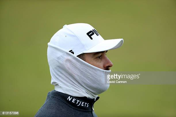Louis Oosthuizen of South Africa feels the cold easterly wind after his second shot at the 18th hole during the second round of the Alfred Dunhill...