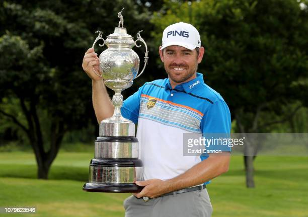 Louis Oosthuizen of South Africa holds the trophy after his six shot win in the final round of the South African Open on the Firethorn Course at...
