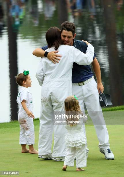 Louis Oosthuizen of South Africa hugs his wife NelMare as his daughters look on during the Par 3 Contest prior to the start of the 2017 Masters...