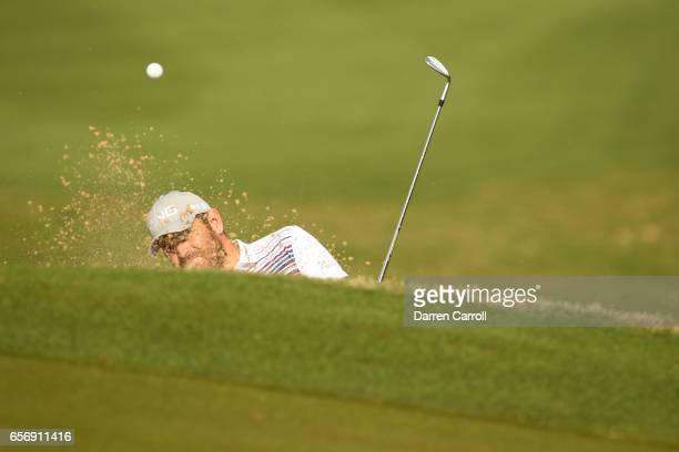 Louis Oosthuizen of South Africa plays a shot out of a bunker on the 1st hole of his match during round two of the World Golf ChampionshipsDell...
