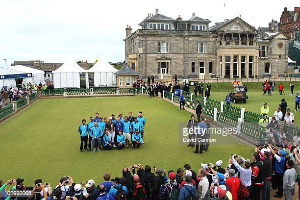 Louis Oosthuizen of South Africa poses with the greens staff and the Claret Jug after his sevenstroke victory at the 139th Open Championship on the...