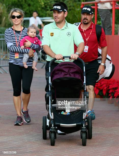Louis Oosthuizen of South Africa pushes a pram as he walks with his wife NelMare Oosthuizen and caddie Wynand Stander following the second round of...