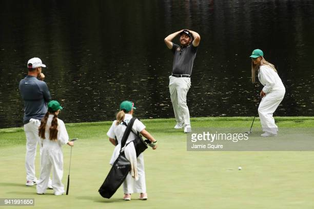 Louis Oosthuizen of South Africa reacts as his wife NelMare Oosthuizen putts during the Par 3 Contest prior to the start of the 2018 Masters...