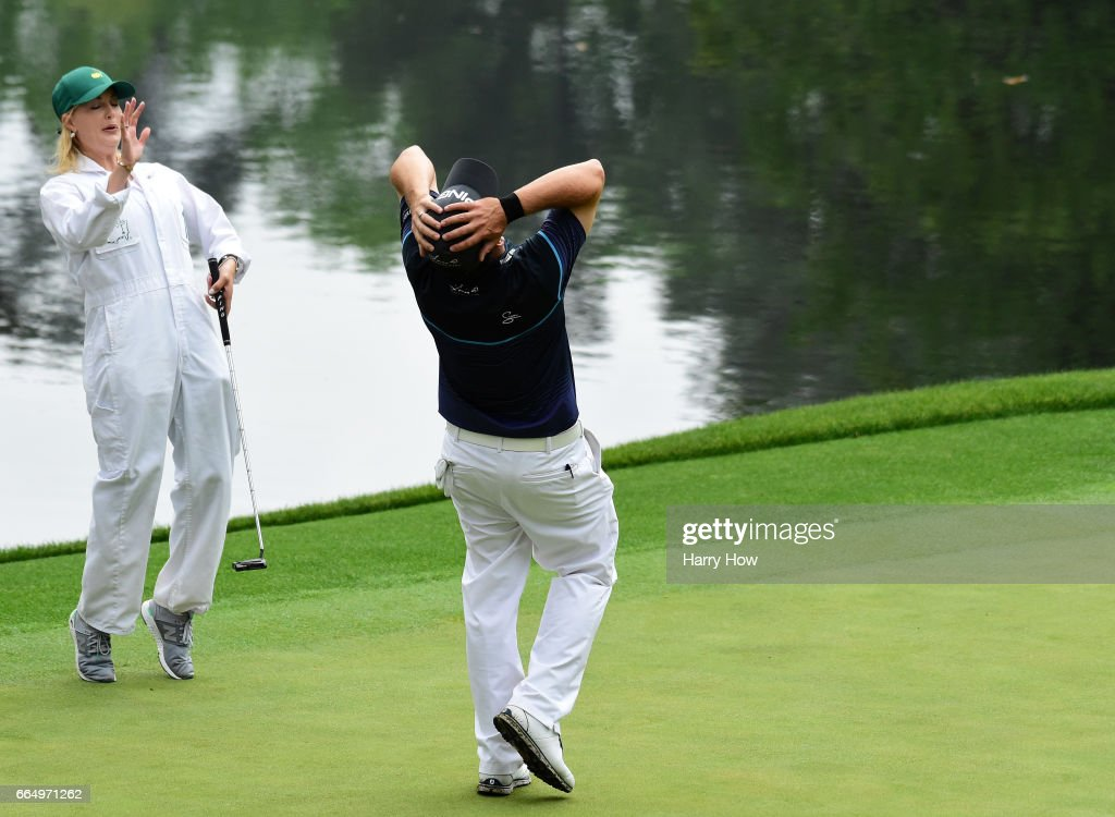 Louis Oosthuizen of South Africa reacts to a putt by Rosalind, wife of Charl Schwartzel of South Africa, during the Par 3 Contest prior to the start of the 2017 Masters Tournament at Augusta National Golf Club on April 5, 2017 in Augusta, Georgia. The Par 3 Contest was later cancelled due to inclement weather.