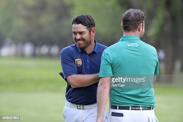 Louis Oosthuizen of South Africa shakes hands with Branden Grace of South Africa after making a par on the 18th hole during the first round of World...