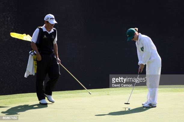 Louis Oosthuizen of South Africa walks across a green with his wife NelMare during the Par 3 Contest prior to the 2009 Masters Tournament at Augusta...