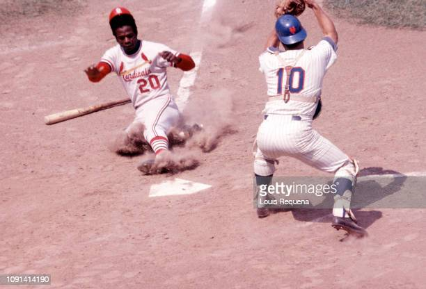 Louis Requena of the St Louis Cardinals slides safely into home ahead of the tag by Duffy Dyer of the New York Mets at Shea Stadium on an unknown...