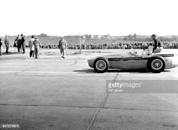 Louis Rosier driving a maserati on the grid with a passenger sat on the back at the Berlin Grand Prix 1954