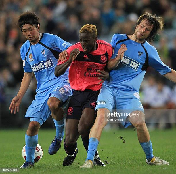 Louis Saha of Everton is sandwiched between two Sydney FC players during a preseason friendly match between Sydney FC and Everton FC at ANZ Stadium...