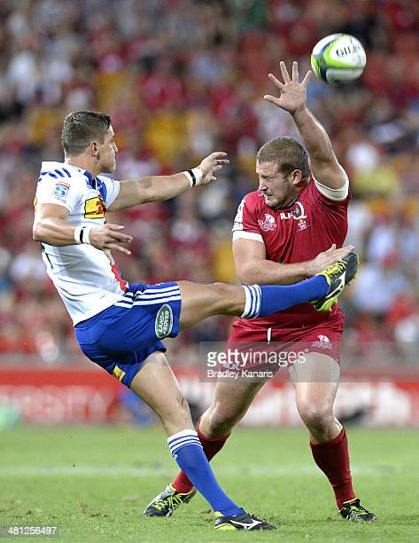 Louis Schreuder of the Stormers gets a kick away as Greg Holmes of the Reds attempts a charge down during the round seven Super Rugby match between...