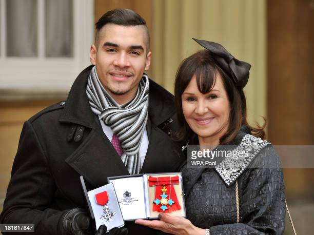 Louis Smith MBE and Arlene Phillips CBE hold their medals after they were presented to them by Queen Elizabeth II at the Investiture Ceremony at...
