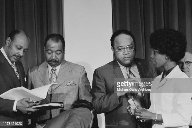 Louis Stokes George W Collins Charles C Diggs Jr and Shirley Chisholm talking at a meeting of the Congressional Black Caucus