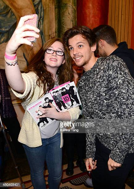 Louis Tomlinson of One Direction poses for a picture with a fan as he attends the book signing of One Direction's new book 'Where We Are' held at...