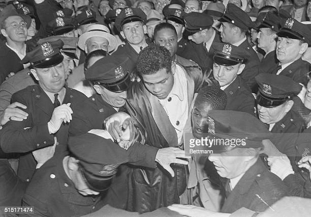 Louis trods path of glory to dressing roomSurrounded by a big squad of policemen Joe Louis makes his way to the dressing room in the Yankee Stadium...