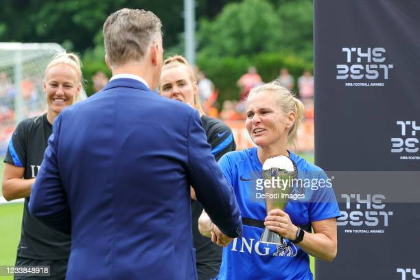 Louis van Gaal and Sarina Wiegman of Netherlands gives a trophy during the training session of Netherlands Women at Mac3Park Stadium on July 03, 2021...