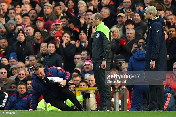 Louis van Gaal Manager of Manchester United makes a point to the fourth official with Arsene Wenger Manager of Arsenal during the Barclays Premier...