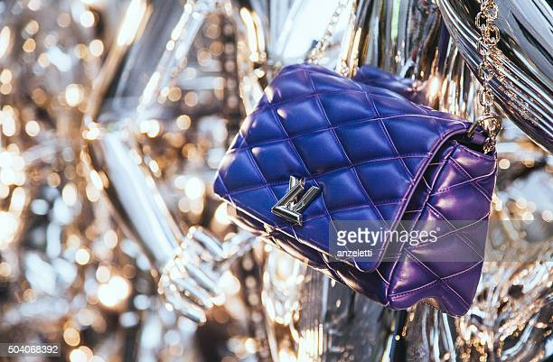 louis vuitton bag in a shop window in via montenapoleone - louis vuitton designer label stock photos and pictures