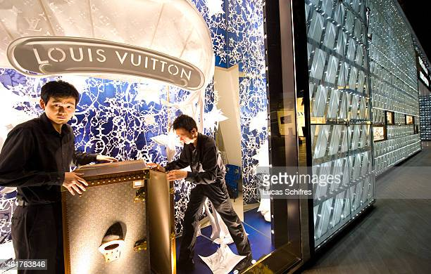 Louis Vuitton staffs arrange the store's window display in the International Finance Center shopping mall on August 19 2009 in Luziajui Pudong...