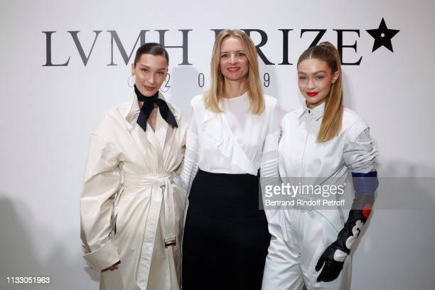 Louis Vuitton's executive vice president Delphine Arnault standing between models Bella Hadid and her sister Gigi Hadid attend the LVMH Prize 2019...
