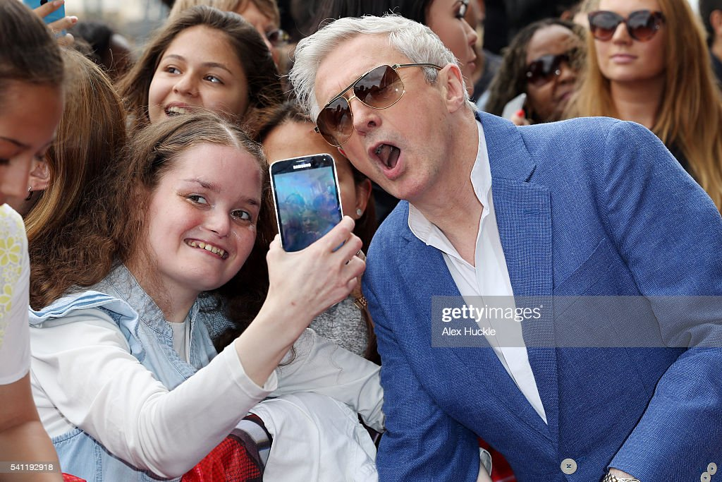 Louis Walsh poses for selfies with fans as he attends the X Factor Auditions on June 19, 2016 in London, England.