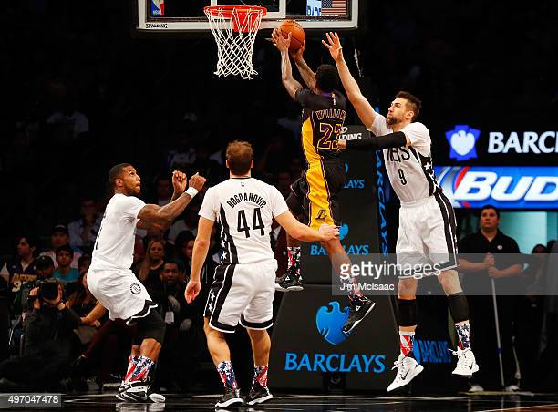 Louis Williams of the Los Angeles Lakers in action against Thomas Robinson Andrea Bargnani and Bojan Bogdanovic of the Brooklyn Nets at Barclays...