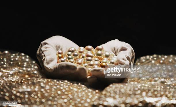 Louise Berg touring exhibitions coordinator for the Australian Museum holds a portion of a consignment of 6000 pearls which are to be added to the...