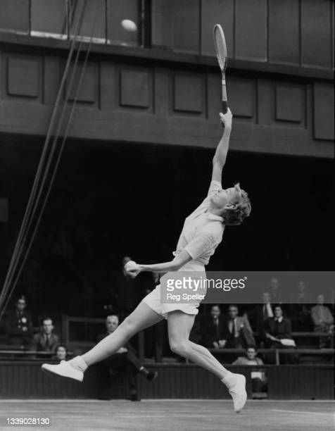 Louise Brough of the United States jumps to play an overhead return to Angela Mortimer of Great Britain during their Women's Singles Quarterfinal...