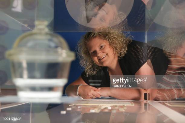 Louise Brown who in 1978 became the world's first baby to be born following successful in vitro fertilisation poses with a glass desiccator a jar...