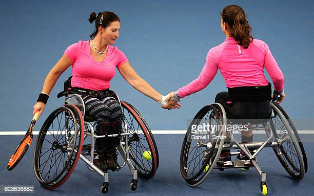 Louise Hunt of Great Britain and Kgothatso Montjane of South Africa tap hands between points in their women's doubles match against Sarah Gaisford of...