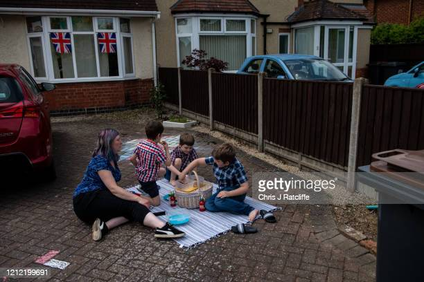 Louise Jackson and her sons Dougie, Floyd and Dylan, have a picnic on their drive during a socially distanced street party for VE Day on May 8, 2020...