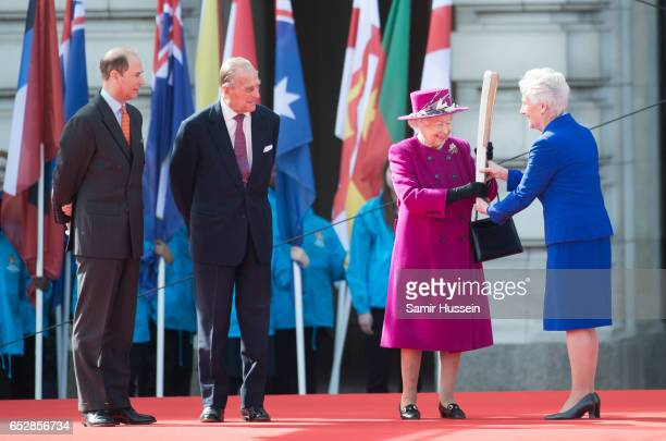 Louise Martin President of the Commonwealth Games Federation hands Queen Elizabeth II the Commonwealth baton as Prince Philip Duke of Edinburgh and...