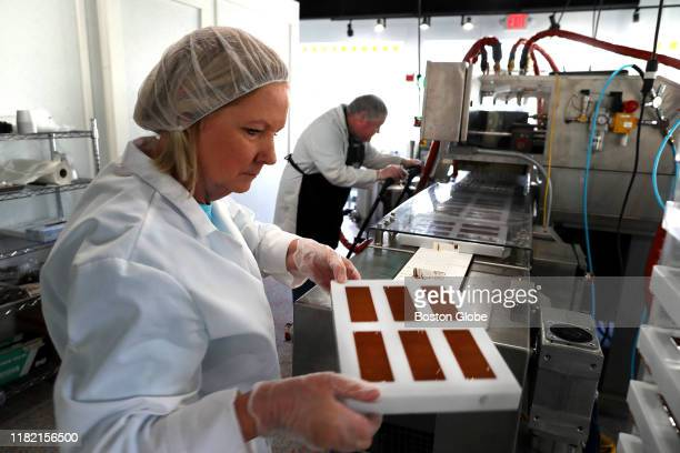 Louise Mawhinney lifts a tray of Sky Bars that were just filled and formed in molds off of the conveyor belt as her son Frank Mawhinney runs the...