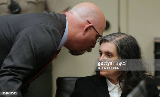 Louise Turpin listens to lawyer Jeff Moore while appearing in court with husband David and their lawyers on January 24 2018 in Riverside California...